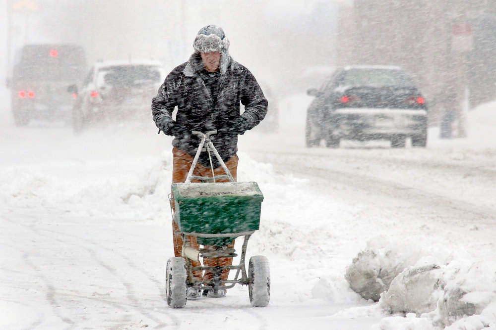 . J & J Lawn Service employee Calvin Parker helps clear a sidewalk in downtown Marion, Ind., on Wednesday, Dec. 26, 2012. (AP Photo/Chronicle-Tribune, Jeff Morehead)