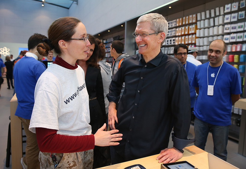 . Apple CEO Tim Cook (R) talks with Dorothy Arndt (L) who just purchased the new iPhone on September 20, 2013 in Palo Alto, California.  (Photo by Justin Sullivan/Getty Images)