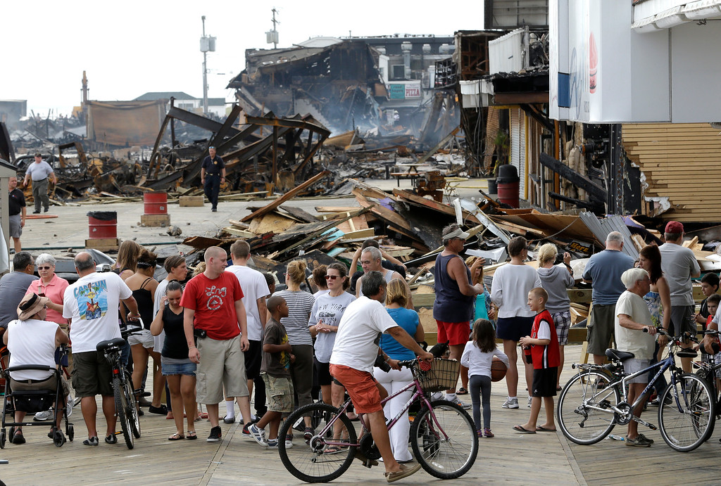. People gather at a barricade to catch a glimpse of the destruction left behind a day after a massive fire burned a large portion of the Seaside Park boardwalk, Friday, Sept. 13, 2013, in Seaside Park, N.J. (AP Photo/Julio Cortez)