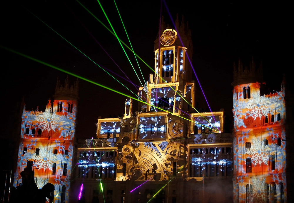 Description of . Laser beams and images are projected on the facade of Madrid's city hall during a lighting show to mark the start of Christmas festivities in Spain on December 23, 2012. REUTERS/Sergio Perez
