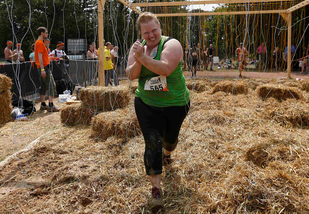 ". Heather Cozad of the U.S. runs through the ""Electroshock Therapy\"" obstacle made of hanging electrical wire holding some 10,000 Volts in the finish of the \""Tough Mudder\"" endurance event series in the Fursten Forest, a former British Army training ground near the north-western German city of Osnabrueck July 13, 2013. The hardcore but un-timed event over 16 km (10 miles) was designed by British Special Forces to test mental as well as physical strength. Some 4,000 competitors had to overcome obstacles of common human fears, such as fire, water, electricity and heights. REUTERS/Wolfgang Rattay"
