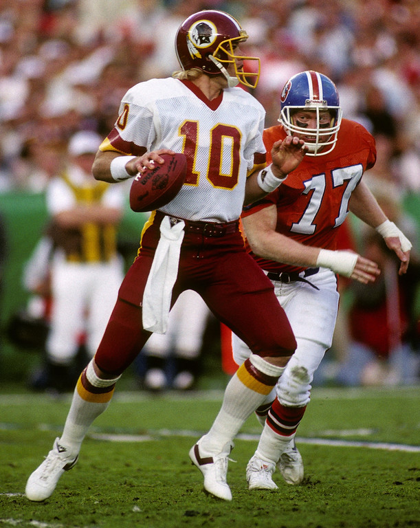 . Quarterback Jay Schroeder #10 of the Washington Redskins drops back to pass under pressure from defensive end Karl Mecklenburg #77 of the Denver Broncos during Super Bowl XXII at Jack Murphy Stadium on January 31, 1988 in San Diego, California.    (Photo by George Rose/Getty Images)