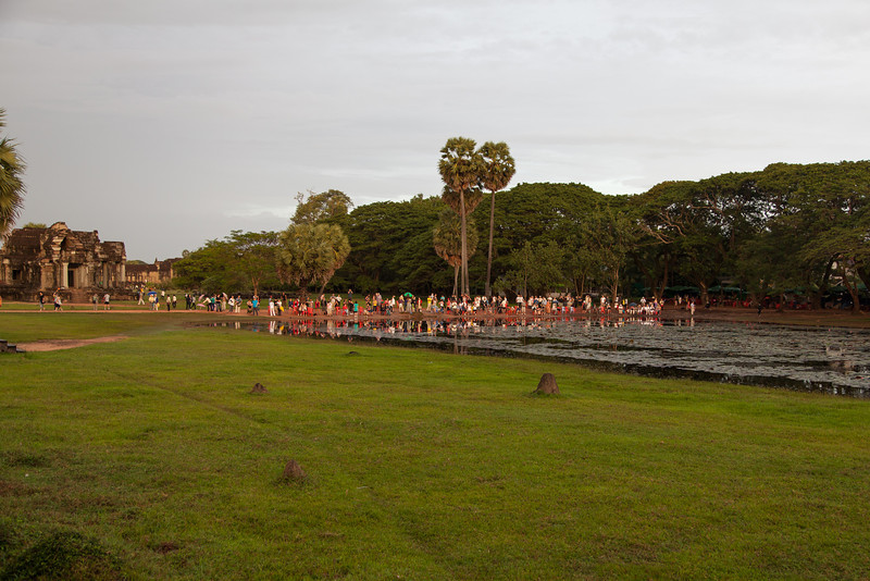 A crowd of tourists watching sunrise over Angkor Wat, presumably trying to catch a reflection in the pond.