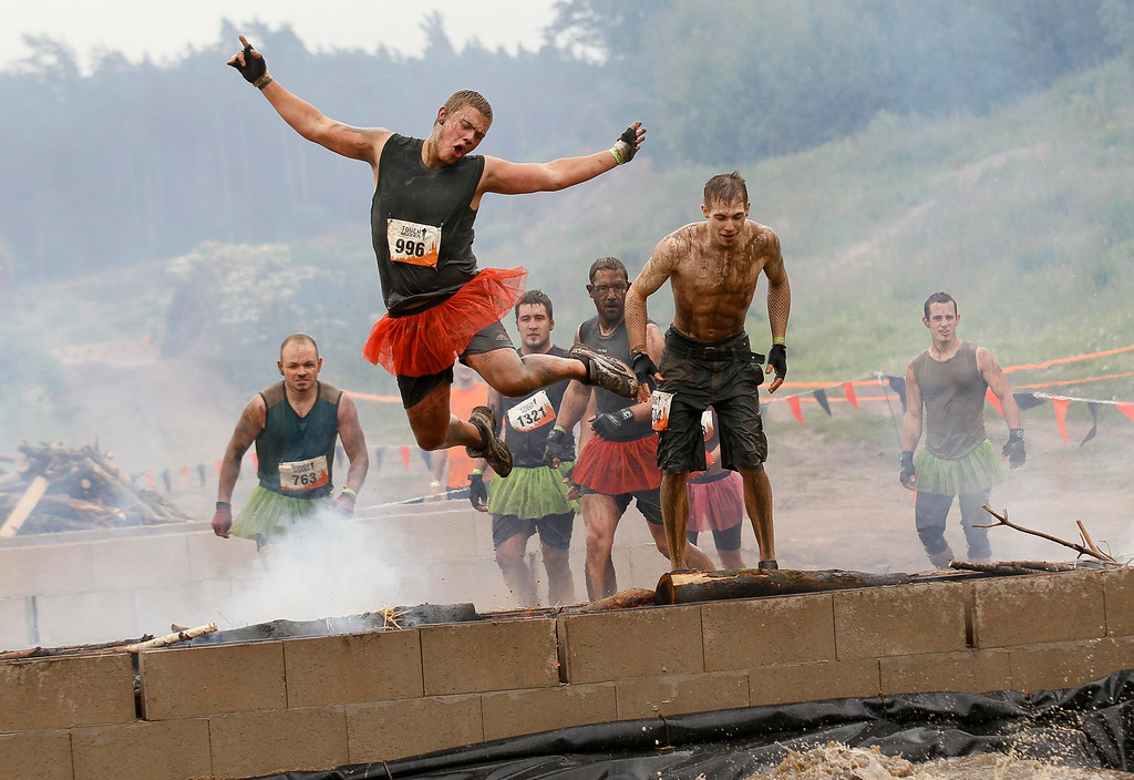 """. A participant of the \""""Tough Mudder\"""" endurance event series jumps over an open fire into a puddle at the \""""Fire Walker\"""" obstacle in the Fursten Forest, a former British Army training ground near the north-western German city of Osnabrueck July 13, 2013. The hardcore but un-timed event over 16 km (10 miles) was designed by British Special Forces to test mental as well as physical strength. Some 4,000 competitors had to overcome obstacles of common human fears, such as fire, water, electricity and heights.   REUTERS/Wolfgang Rattay"""