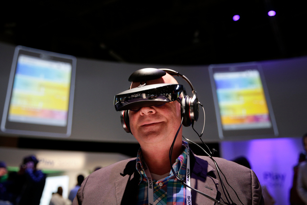 Description of . Juergen Boyny, of Germany, watches a video clip with a personal viewing device at the Sony booth at the International Consumer Electronics Show(CES) on Thursday, Jan. 9, 2014, in Las Vegas. (AP Photo/Jae C. Hong)