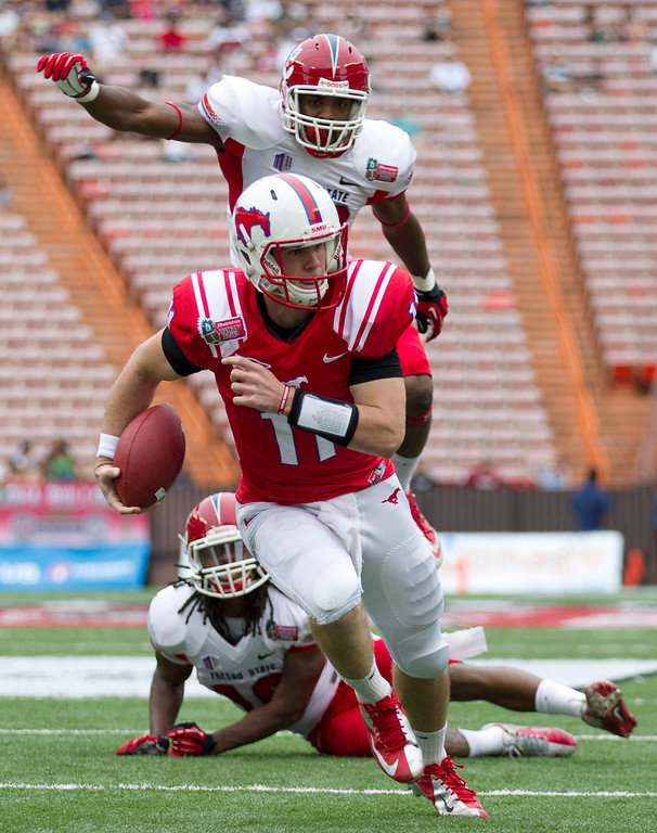 . Fresno State safety Phillip Thomas, bottom, and linebacker Tristan Okpalaugo, top, watch as SMU quarterback Garrett Gilbert (11) breaks a tackle and runs in for a touchdown in the second quarter of the Hawaii Bowl NCAA college football game Monday, Dec. 24, 2012, in Honolulu. (AP Photo/Eugene Tanner)
