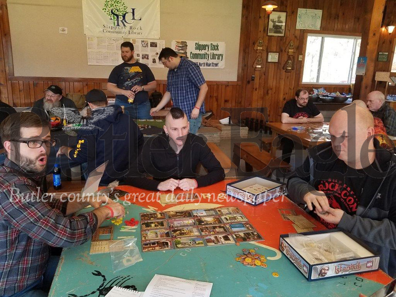 Jim Smith photoFrom left, Peter Bess of Butler, Dave Spik of Pittsburgh and James Wilson of Butler play a tabletop game Saturday during Slippery Rock-Con, a game and pop culture convention held this weekend at Camp Bucoco in Slippery Rock Township. 3 col pic