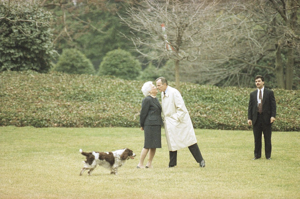 . President George Bush, departing for a week long campaign trip, gets a kiss from wife Barbara on the South Lawn of the White House in Washington, Wednesday, March 4, 1992. Bush, in the first three days of the trip, will travel to Florida, South Carolina, Tennessee, Oklahoma, Louisiana and Mississippi Family dog Millie looks on. (AP Photo/Barry Thumma)