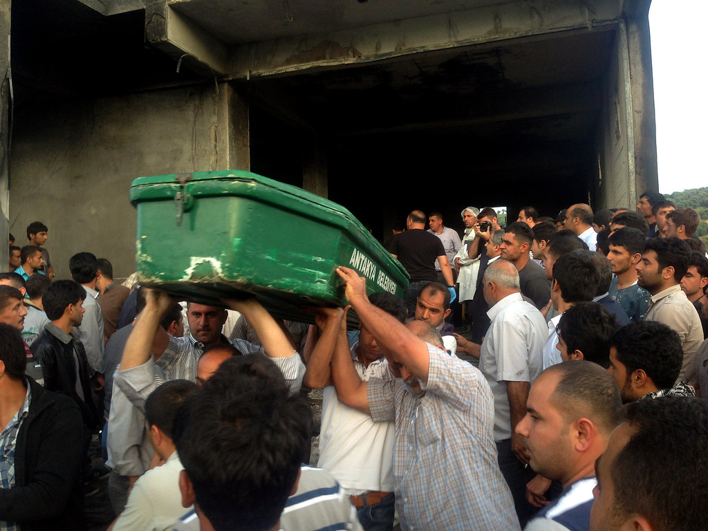 . Men carry a coffin on May 17, 2013, after suspects set ablaze an illegal fuel depot located in the basement of a three-storey building in a small village near Turkey\'s border with Syria, triggering a strong explosion that killed at least ten people and wounded nine others. Among the wounded were three suspected smugglers as well as several security officers, Anatolia news agency reported.  STR/AFP/Getty Images