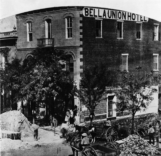 View of the Bella Union Hotel in Los Angeles, showing workers around mounded dirt and rubble, ca.1865