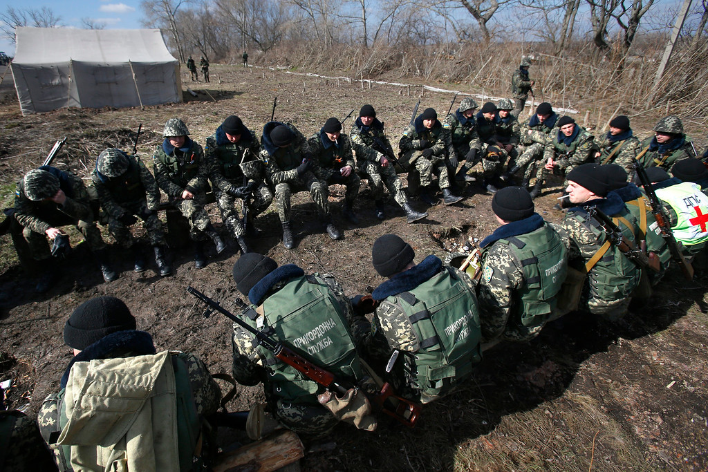 . Ukrainian border guards take a break during a training session at a military camp in the village of Alekseyevka on the Ukrainian-Russian border, eastern Ukraine, Friday, March 21, 2014. Russian President Vladimir Putin signed bills on Friday making Crimea part of Russia, completing the annexation from Ukraine. (AP Photo/Sergei Grits)