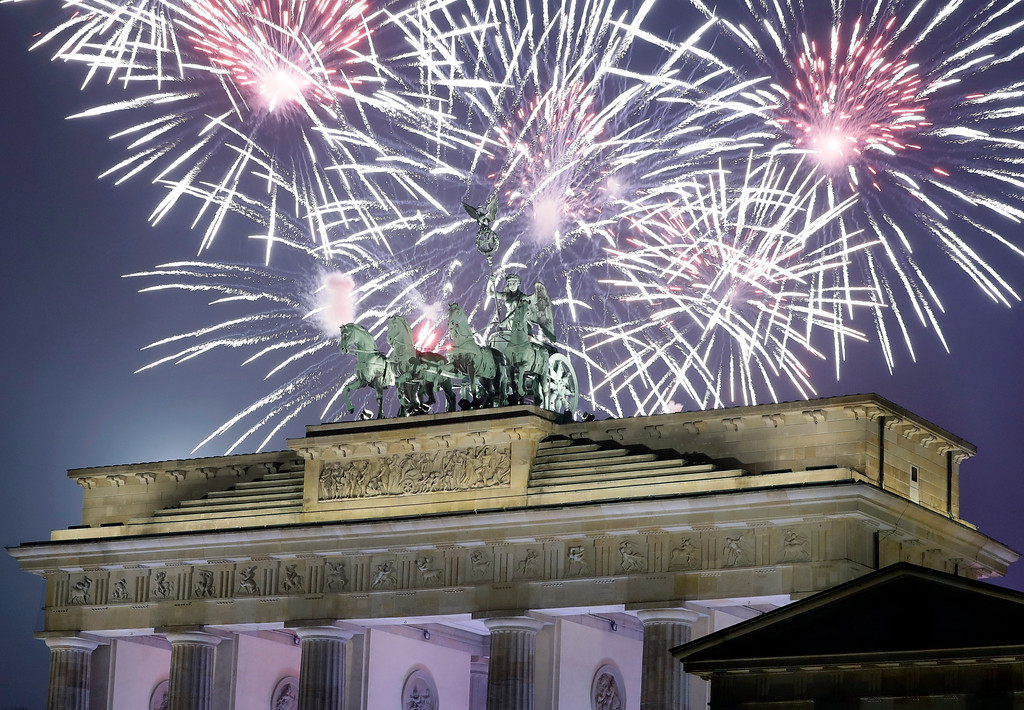. Fireworks light the sky above the Quadriga at the Brandenburg Gate shortly after midnight in Berlin, Germany, Sunday, Jan. 1, 2017. Hundred thousands of people celebrated New Year\'s Eve welcoming the new year 2017 in Germany\'s capital. (AP Photo/Michael Sohn)