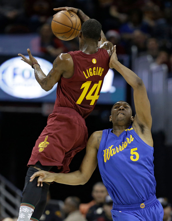 . Golden State Warriors\' Kevon Looney (5) fouls Cleveland Cavaliers\' DeAndre Liggins (14) in the first half of an NBA basketball game, Sunday, Dec. 25, 2016, in Cleveland. The Cavaliers won 109-108. (AP Photo/Tony Dejak)