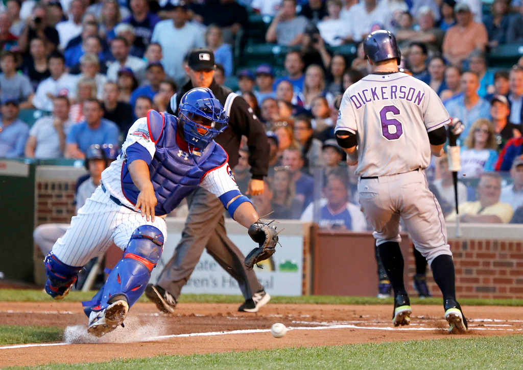 . Colorado Rockies\' Corey Dickerson (6) scores past Chicago Cubs catcher Welington Castillo on a double by Nolan Arenado during the first inning of a baseball game Tuesday, July 29, 2014, in Chicago. (AP Photo/Charles Rex Arbogast)