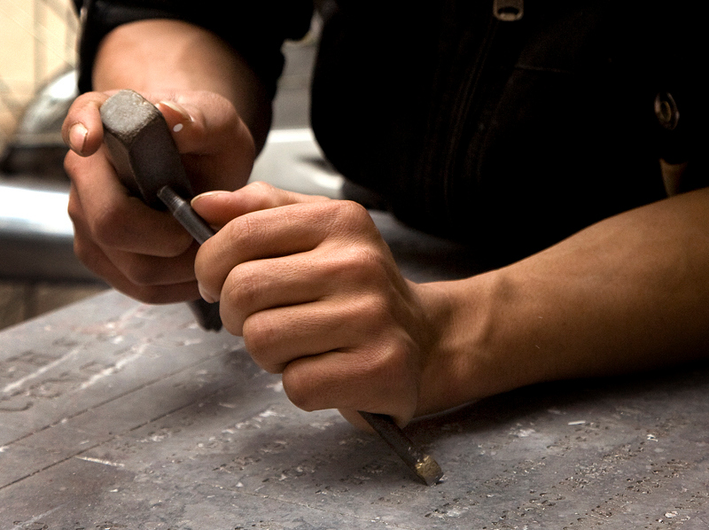 The hands of a stone carver, engraving a headstone