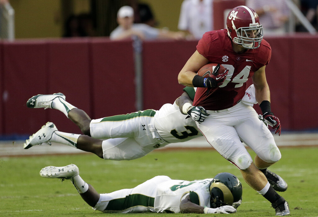 . Alabama tight end Brian Vogler (84) pulls out of the tackle of Colorado State cornerback Shaq Bell (3) and defensive back Bernard Blake (23) during the first half of an NCAA college football game in Tuscaloosa, Ala., Saturday, Sept. 21, 2013. (AP Photo/Dave Martin)