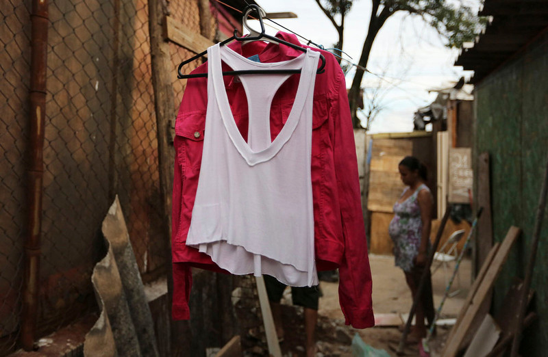 . Laundry is hung out to dry next to a woman from Brazil\'s Movimento dos Sem-Teto (Roofless Movement) at an area that used to be a nursery and school in Sao Paulo March 10, 2013. More than 1,200 people from Brazil\'s roofless movement live in an explosion prone area that has been contaminated with methane since October 2012, local media reported. According to the Environmental Sanitation Technology Company in the State of Sao Paulo (CETESB) the soil and water from the groundwater are contaminated with methane. REUTERS/Nacho Doce