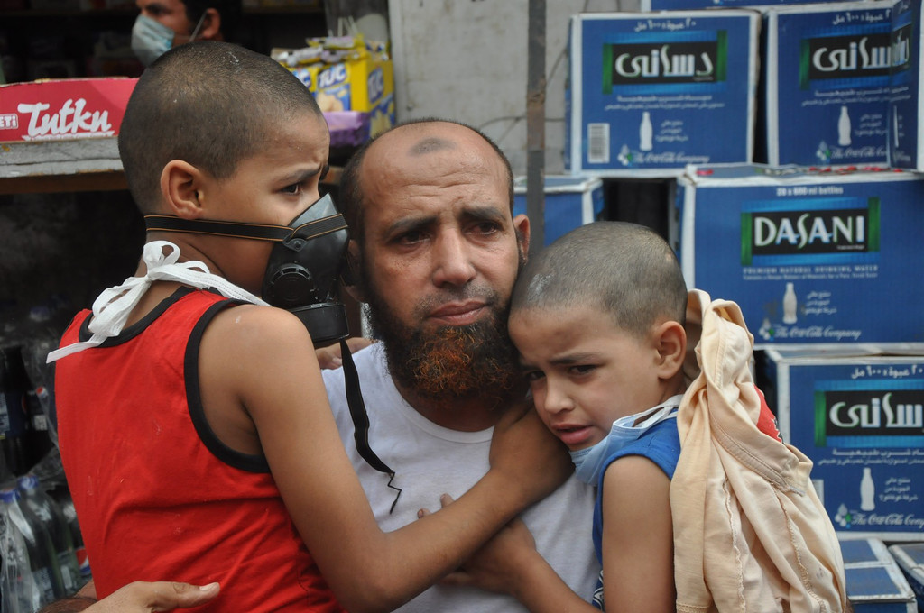 . Two boys hold on to a supporter of ousted Islamist President Mohammed Morsi as Egyptian security forces clear a sit-in camp set up near Cairo University in Cairo\'s Giza district, Egypt, Wednesday, Aug. 14, 2013.  (AP Photo/Hussein Tallal)