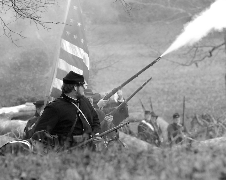 """Reenactors for the 12th Indiana Infantry """"surprise"""" the Confederate reenactors near a hill on the battlefield. The Skirmish at Gamble's Hotel happened on March 5, 1885 when 500 federal soldiers, under the command of Reuben Williams of the 12th Indiana Infantry, marched into Florence to destroy the railroad depot but were met by Confederate soldiers backed up with 400 militia. The reenactment, held by the 23rd South Carolina Infantry, was held at the Rankin Plantation in Florence, South Carolina on Saturday, March 5, 2011. Photo Copyright 2011 Jason Barnette"""