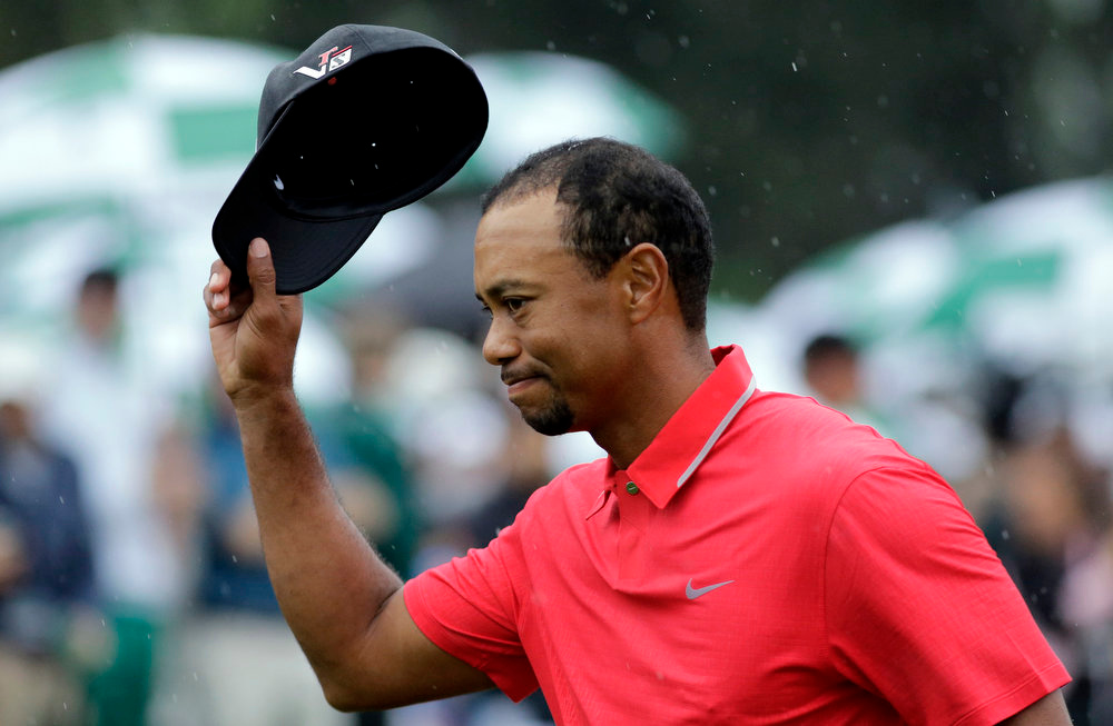 Description of . Tiger Woods tips his cap after putting out on the 18th hole during the fourth round of the Masters golf tournament Sunday, April 14, 2013, in Augusta, Ga. (AP Photo/Matt Slocum)