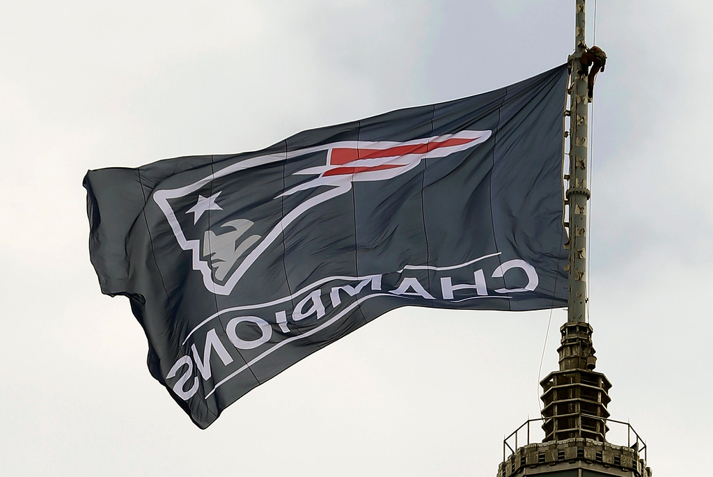 . A worker secures a New England Patriots flag on a flagpole atop a building prior to a victory parade in Boston Wednesday, Feb. 4, 2015, to honor the Patriots win over the Seattle Seahawks 28-24 in Super Bowl XLIX Sunday, in Glendale, Ariz. (AP Photo/Steven Senne)