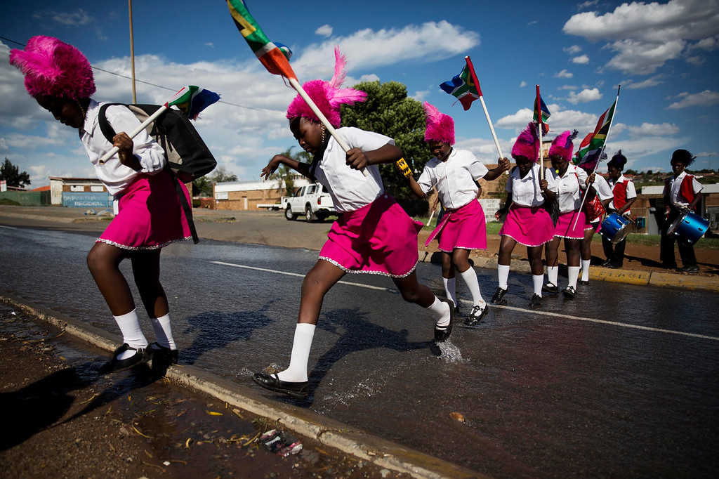 . Drum majorettes negotiate their way through water flowing down a street en route to Vilakazi Street in the Soweto township, Johannesburg, South Africa, Sunday, Dec. 15, 2013.  Anti-apartheid champion Nelson Mandela was buried in his home village on Sunday after a funeral that mixed ancient tribal rituals with a display of the might of the new, integrated South Africa.  (AP Photo/Matt Dunham)
