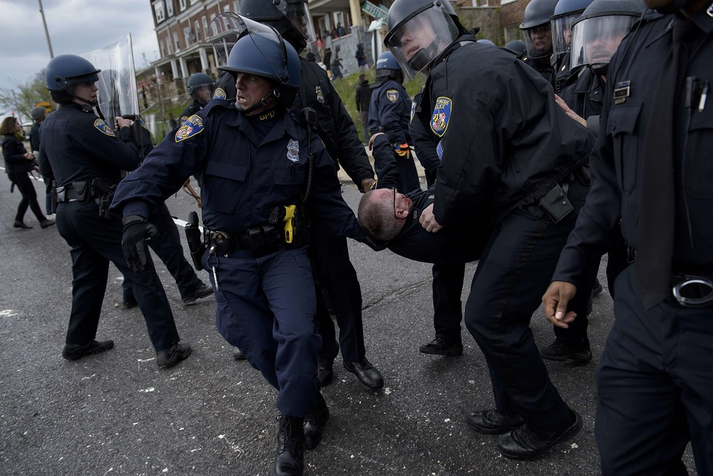 . Baltimore police officers carry an injured comrade as they clash with protesters in the streets near Mondawmin Mall April 27, 2015 in Baltimore, Maryland. Violent street clashes erupted in Baltimore on Monday after friends and family gathered for the funeral of Freddie Gray, a 25-year-old black man whose death in custody triggered a fresh wave of protests over US police tactics. Police said at least seven officers were injured -- one of them was unresponsive -- as youths hurled bricks and bottles and destroyed at least one police vehicle in the vicinity of the shopping mall not far from the church where the funeral took place.  BRENDAN SMIALOWSKI/AFP/Getty Images