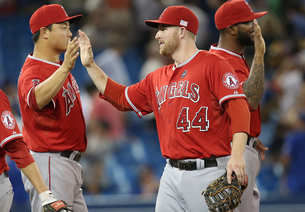 . TORONTO, CANADA - SEPTEMBER 11: Mark Trumbo #44 of the Los Angeles Angels of Anaheim celebrates their victory with Hank Conger #16 during MLB game action against the Toronto Blue Jays on September 11, 2013 at Rogers Centre in Toronto, Ontario, Canada. (Photo by Tom Szczerbowski/Getty Images)