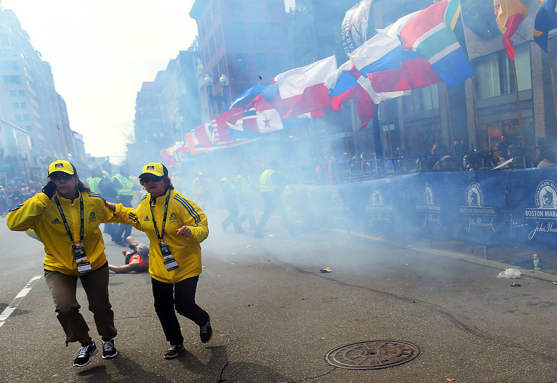 . People react to an explosion at the 2013 Boston Marathon in Boston, Monday, April 15, 2013. Two explosions shattered the euphoria of the Boston Marathon finish line on Monday, sending authorities out on the course to carry off the injured while the stragglers were rerouted away from the smoking site of the blasts. (AP Photo/The Boston Globe,  John Tlumacki)