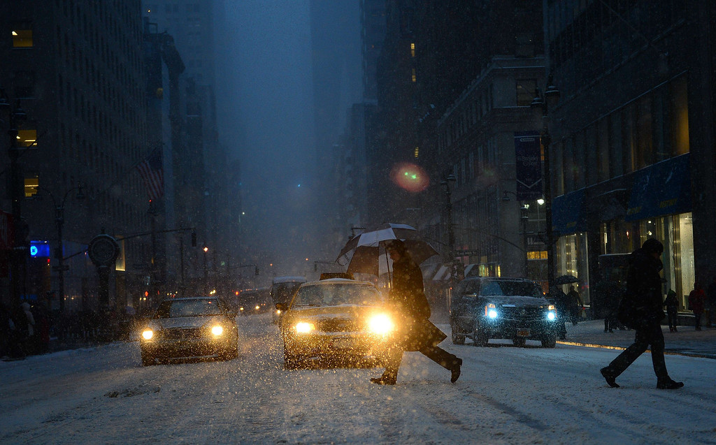 . People walk during a snow storm in New York, January 21, 2014. In New York, a storm alert was issue for noon (1700 GMT) Tuesday to 6:00 am (1100 GMT) Wednesday with as much as a foot (30 centimeters) forecast for the metropolitan region. AFP PHOTO/Emmanuel DUNAND/AFP/Getty Images