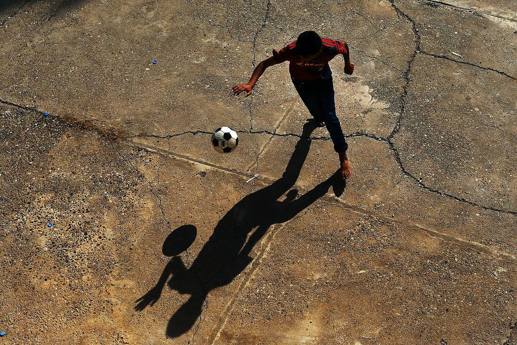 . ERBIL, IRAQ - JUNE 27: A displaced Iraqi Christian plays soccer in the courtyard of Saint Joseph\'s church after having to flee his district with hundreds of others on June 26, 2014 in Erbil, Iraq.Tens of thousands of people have fled Iraq\'s second largest city of Mosul after it was overrun by ISIS (Islamic State of Iraq and Syria) militants. Many have been temporarily housed at various IDP  camps around the region including the area close to Erbil, as they hope to enter the safety of the nearby Kurdish region. Christians, Shiites and Kurdish Iraqis have received the brunt of the violence from the militants.  (Photo by Spencer Platt/Getty Images)