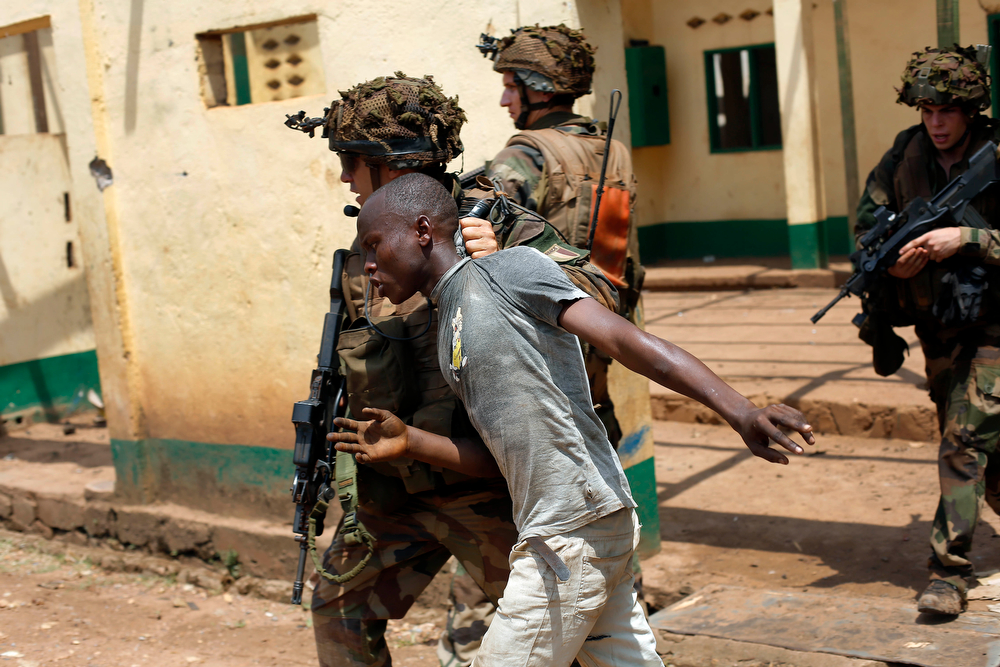 . French forces grab a man looting a mosque before chasing him away in the Miskin district of  Bangui, Central African Republic, Monday Feb. 3, 2014. Fighting between Muslim Seleka militias and Christian anti-Balaka factions continues as French and African Union forces struggle to contain the bloodshed. (AP Photo/Jerome Delay)