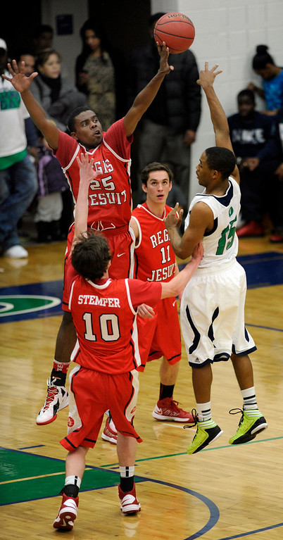 . Raiders center Elijah Sanford (25) hot a hand on a shot from Blazers guard Reginald Gibson (15) in the first half. The Overland High School boy\'s basketball team defeated Regis Jesuit 80-66 Tuesday night, December 11, 2012.  Karl Gehring/The Denver Post