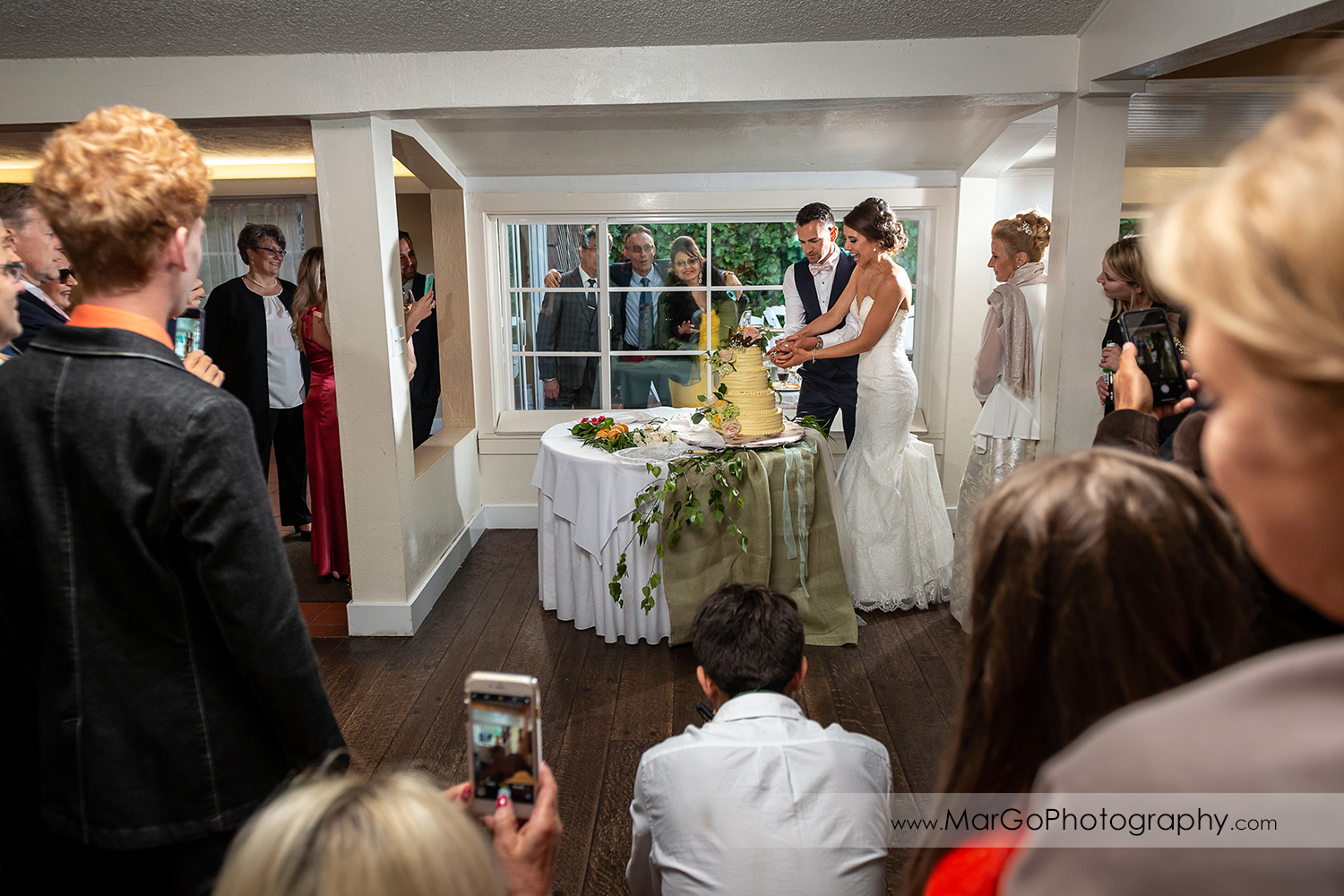 bride and groom cutting wedding cake during reception at San Pablo Rockefeller Lodge