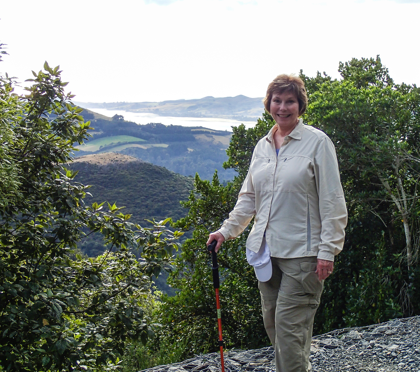 A woman hiker poses on a hike in Dunedin, New Zealand.