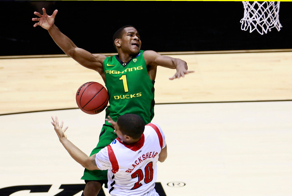 . Oregon Ducks guard Dominic Artis (1) loses the ball as he goes to the basket against Louisville Cardinals guard/forward Wayne Blackshear (20) during their Midwest Regional NCAA men\'s basketball game in Indianapolis, Indiana, March 29, 2013. REUTERS/Brent Smith