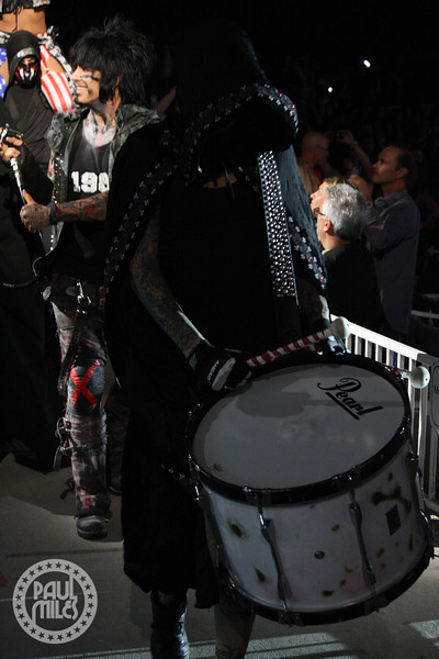 A hooded Tommy Lee enters the stage via a procession through the crowd, with Nikki Sixx behind him.