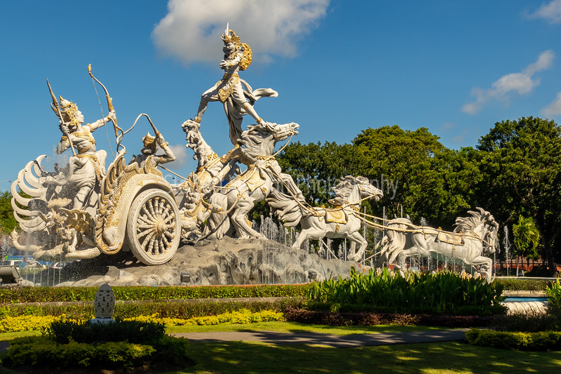 This statue sits in the middle of a very busy round-a-bout near the Ngurah Rai international airport, that is intersected by the main roads leading to Denpasar, Nusa Dua, Sanur and Uluwatu. This statue depicts a scene from the ancient Hindu text called Ramayana, whereby the Divine Prince Rama is rescuing his wife, Sita, from the demon King, Ravana. As seen here, Prince Rama is standing in the chariot and holding Sita while aiming an arrow mounted in a bow at the demon King who is standing on 2 of the horses drawing the chariot.