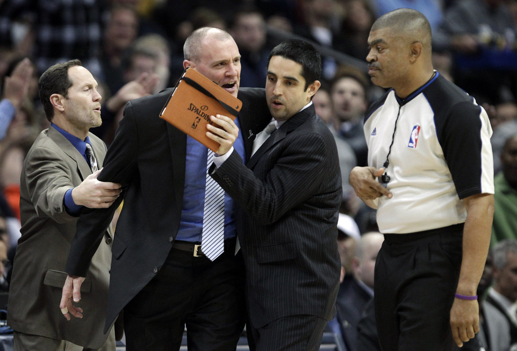 . Dallas Mavericks assistant coaches Monte Mathis, left, and Kaleb Canales, third from left, try to separate coach Rick Carlisle from referee Tony Brothers, right, moments before Carlisle was issued a second technical foul and ejected in the second quarter of an NBA basketball game in Denver on Saturday, Nov. 23, 2013. (AP Photo/Joe Mahoney)