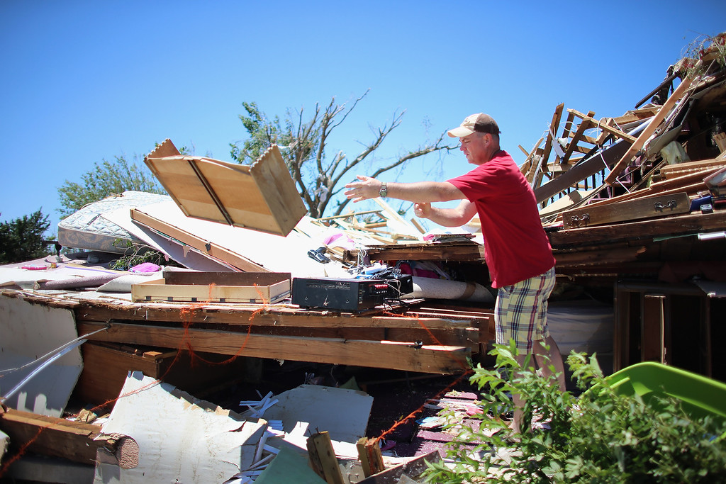 . EL RENO, OK - JUNE 01:  William Miles looks for items to salvage from a home destroyed when a tornado hit on June 1, 2013 in El Reno, Oklahoma. The tornado ripped through the area last night killing at least nine people, injuring many others and destroying homes and buildings.  (Photo by Joe Raedle/Getty Images)