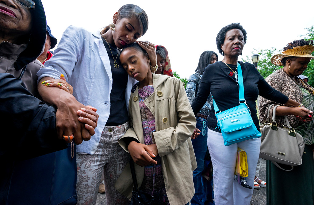 . People gathered at a rally held by the Greater Allen A.M.E. Cathedral of New York pray together in the Queens borough of New York Saturday, June 20, 2014, in the wake of the shootings at Emanuel A.M.E. Church in Charleston, S.C. earlier in the week. (AP Photo/Craig Ruttle)