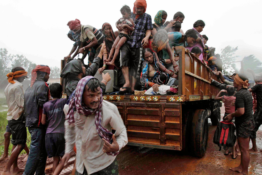 . Evacuated Indian villagers get down from a truck at a relief camp as it rains near Berhampur, India, Saturday, Oct. 12, 2013. Hundreds of thousands of people living along India\'s eastern coastline were taking shelter Saturday from a massive, powerful cyclone Phailin that was set to reach land packing destructive winds and heavy rains. (AP Photo/Bikas Das)
