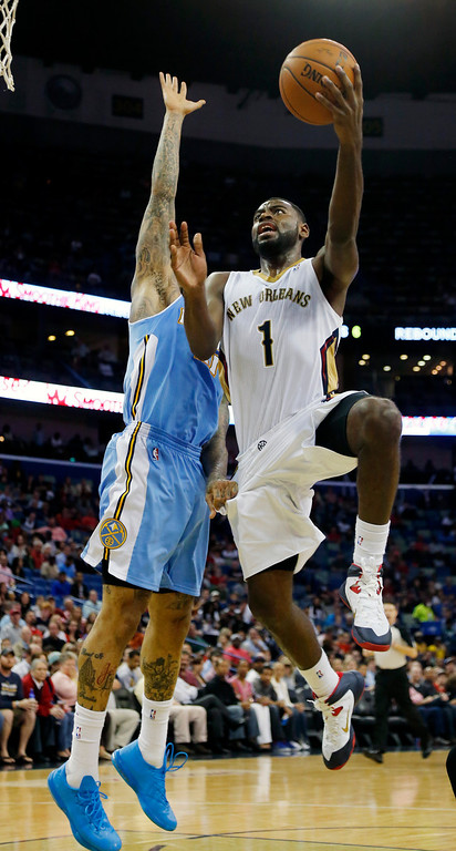 . New Orleans Pelicans small forward Tyreke Evans (1) goes to the basket as Denver Nuggets small forward Wilson Chandler (21) defends in the second half of an NBA basketball game in New Orleans, Sunday, March 9, 2014. The Pelicans defeated the Nuggets 111-107. (AP Photo/Bill Haber)
