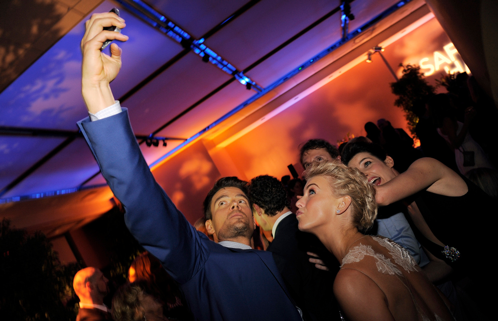 ". Josh Duhamel, left, a cast member in ""Safe Haven,\"" takes a picture of himself with fellow cast members Julianne Hough, second from right, and Cobie Smulders, far right, at the post-premiere party for the film, Tuesday, Feb. 5, 2013 in the Hollywood section of Los Angeles. (Photo by Chris Pizzello/Invision/AP)"