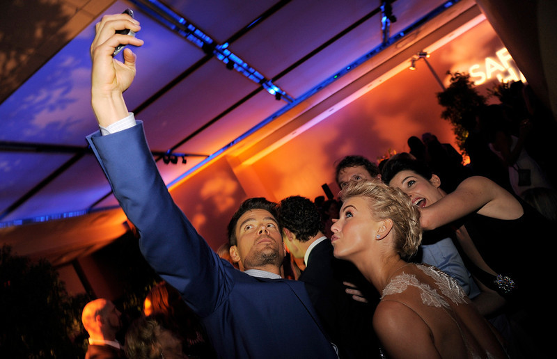 """. Josh Duhamel, left, a cast member in \""""Safe Haven,\"""" takes a picture of himself with fellow cast members Julianne Hough, second from right, and Cobie Smulders, far right, at the post-premiere party for the film, Tuesday, Feb. 5, 2013 in the Hollywood section of Los Angeles. (Photo by Chris Pizzello/Invision/AP)"""