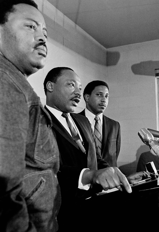 . Dr. Martin Luther King, flanked by Hosea Williams, left, and the Rev. Bernard Lafayette, tells an Atlanta news conference on Tuesday morning January 16, 1968 that his planned march on Washington in April to demand jobs and income for the poor will be led by 3,000 non-violent demonstrators. Williams is field director of the project and Rev. Lafayette is coordinator of the march.(AP Photo/Charles Kelly )