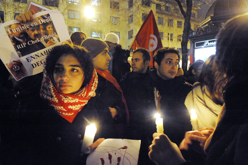 """. A protester holds a poster reading \""""Tunisia in mourning, RIP Chokri Belaid, Ennahdha get out\"""" as others hold candles during a demonstration on February 6, 2013 held outside the Tunisian embassy in Paris against the killing today of prominent Tunisian opposition leader Chokri Belaid. Furious protesters on February 6 erected barricades in central Tunis and hurled rocks at police who tried to disperse them with tear gas in new clashes after the assassination of a prominent opposition figure. MEHDI FEDOUACH/AFP/Getty Images"""