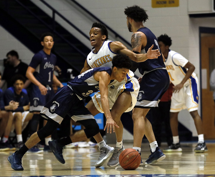Photo by Matt Griffith/VU  Vincennes University's Chuka Mekkam, center , tightly guards Olney Central's Jalen Moore on a drive to the basket Wednesday night in the P.E. Complex.