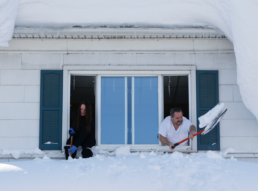 . Residents clear snow from a porch roof while leaning from a second-story window in the south Buffalo area on Friday, Nov. 21, 2014, in Buffalo, N.Y. A snowfall that brought huge drifts and closed roads in the Buffalo area finally ended Friday, yet residents still couldn\'t breathe easy, as the looming threat of rain and higher temperatures through the weekend and beyond raised the possibility of floods and more roofs collapsing under the heavy loads. (AP Photo/Mike Groll)