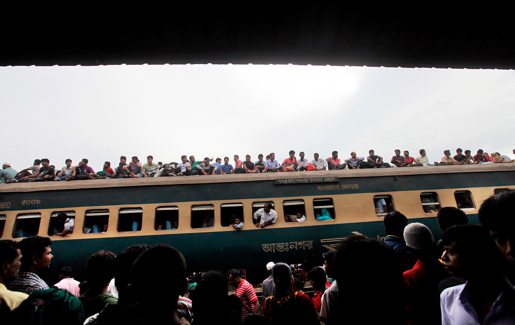 . Bangladeshi Muslims sit on the roof of a packed train bounding for homebound ahead of Eid al-Fitr as others wait at a railway station in Dhaka, Bangladesh, Thursday, Aug. 8, 2013. The mass exodus out of the capital and other major cities in the country is underway as millions are heading back to their home towns to celebrate Eid al-Fitr holiday which marks the end of the holy fasting month of Ramadan. (AP Photo/A.M. Ahad)